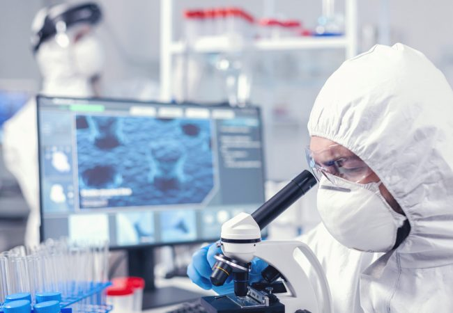 Medical team in laboratory conducting coronavirus analysis using microscope. Scientist in protective suit sitting at workplace using modern medical technology during global epidemic.
