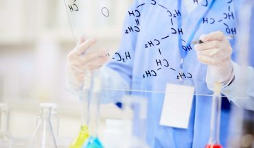 Modern chemist in gloves and uniform writing formulae of molecul